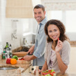 Woman eating while her husband is cooking — Stock Photo #10846260