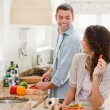 Beautiful woman looking at her husband who is cooking — Stock Photo #10846264