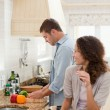 Stock Photo: Beautiful woman looking at her husband who is cooking