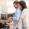 Womhugging her husband while he is cooking — Stock Photo #10846308