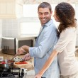 Woman hugging her husband while he is cooking — Stock Photo