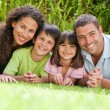 Happy family lying down in the garden — Stock Photo