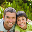 Father with his son lying down in the garden - Foto Stock