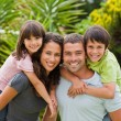 Mother and father giving children a piggyback — Stock Photo