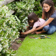Stock Photo: Mother and daughter working in garden