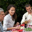 Happy family eating in the garden — Stock Photo #10846492
