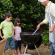 Family  having a barbecue in the garden - Stock Photo