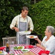 Stock Photo: Man serving his family at the table