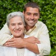 Man hugging his mother in the garden — Stock Photo #10846545