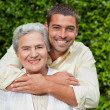 Man hugging his mother in the garden — Stock Photo