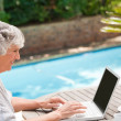 Mature woman working on her laptop — Stock Photo #10846604