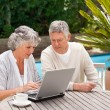 Retired couple working on their laptop — Stockfoto