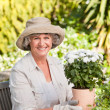 Senior woman with flowers in her garden — Stock Photo #10846617