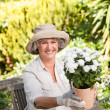Senior woman with flowers in her garden - Stock Photo