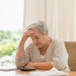Retired woman calculating her domestic bills — Stock Photo #10846659