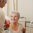 Retired man offering flowers to his wife — Stock Photo #10846674