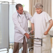 Senior doctor helping his patient to walk — Stock Photo