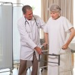 Senior doctor helping his patient to walk — Stock Photo #10846781