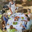 Lovely family eating in the garden — Stock Photo