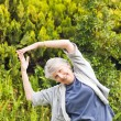 Mature woman doing her streches in the garden - Stock fotografie