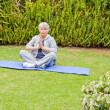 Royalty-Free Stock Photo: Senior woman doing her streches in the garden