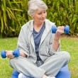 Retired woman doing her exercises in the garden — Stock Photo #10847208