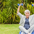 Retired woman doing her exercises in the garden - Stock Photo