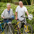 Mature couple walking with their bikes - Stock Photo