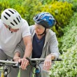 Mature couple mountain biking outside — Stock Photo