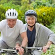 Mature couple mountain biking outside - Foto Stock