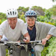 Mature couple mountain biking outside — Stock fotografie