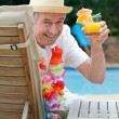 Mature man drinking a cocktail beside the swimming pool — Stock Photo