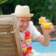Stock Photo: Mature mdrinking cocktail beside swimming pool