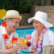 Happy senior couple drinking cocktails and toasting each other — Stock Photo