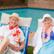 Stock Photo: Senior couple lying down beside swimming pool