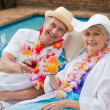 Mature couple drinking a cocktail beside the swimming pool — Stock Photo