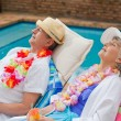 Retired couple sleeping beside the swimming pool — Stock Photo