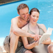 Couple reading a book beside the swimming pool — Stock Photo