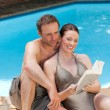 Stock Photo: Couple reading book beside swimming pool