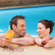 Beautiful couple drinking cocktails in the swimming pool — Stock Photo