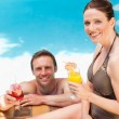 Smiling couple drinking cocktails - Stock Photo
