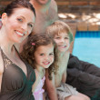 Happy family beside the swimming pool — Stock Photo #10848057