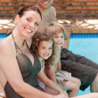 Happy family beside the swimming pool — Stock Photo