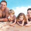 Happy family beside the swimming pool — Stock Photo #10848076