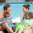 Stock Photo: Portrait of a happy family beside the swimming pool