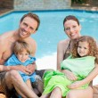 Portrait of a happy family beside the swimming pool — Stock Photo #10848101