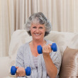 Woman doing her exercises on her sofa — Stock Photo