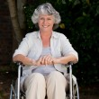 Stock Photo: Smiling womin her wheelchair