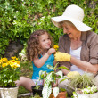 Happy Grandmother with her granddaughter working in the garden - Photo