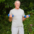 Senior man doing his exercises in the garden — Stock Photo #10848529